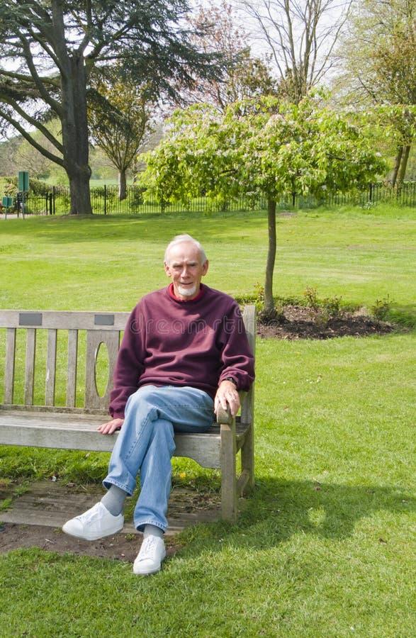 Oude mensenzitting op bank in park stock foto