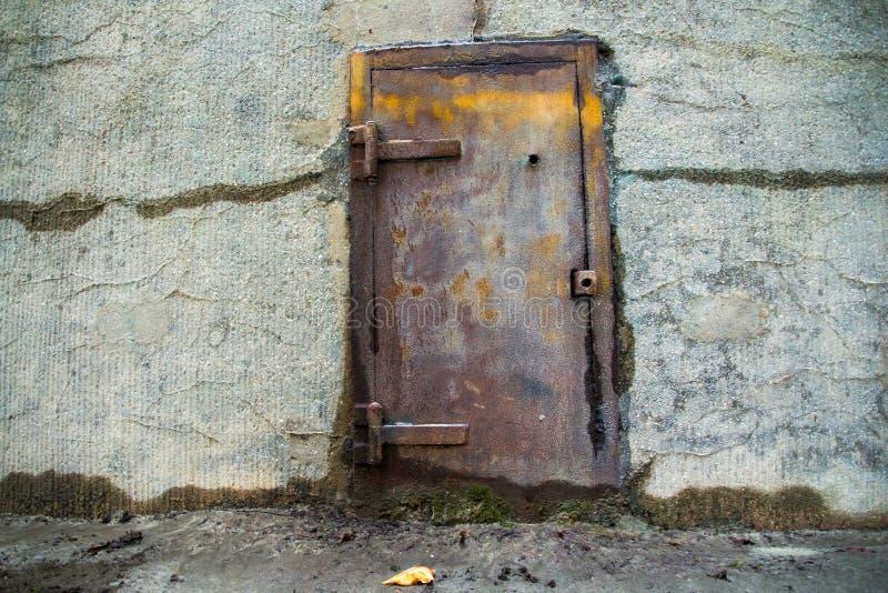 Oude metaaldeur in een concrete muur stock afbeeldingen