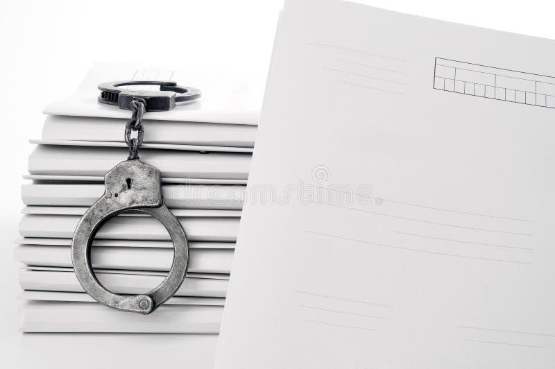 Oude metaalhandcuffs en leeg gevaldossier stock foto