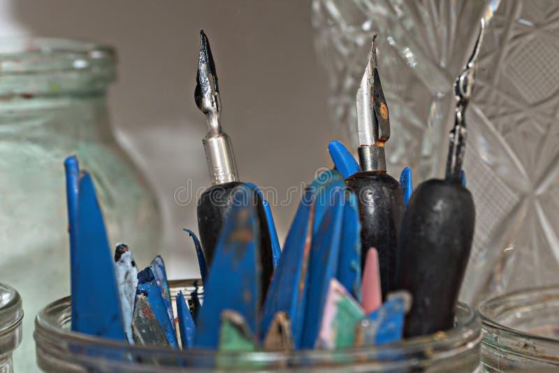 Oude metaalpennen en plastic spatels voor aardewerk in het close-up van de glaskruik stock afbeelding