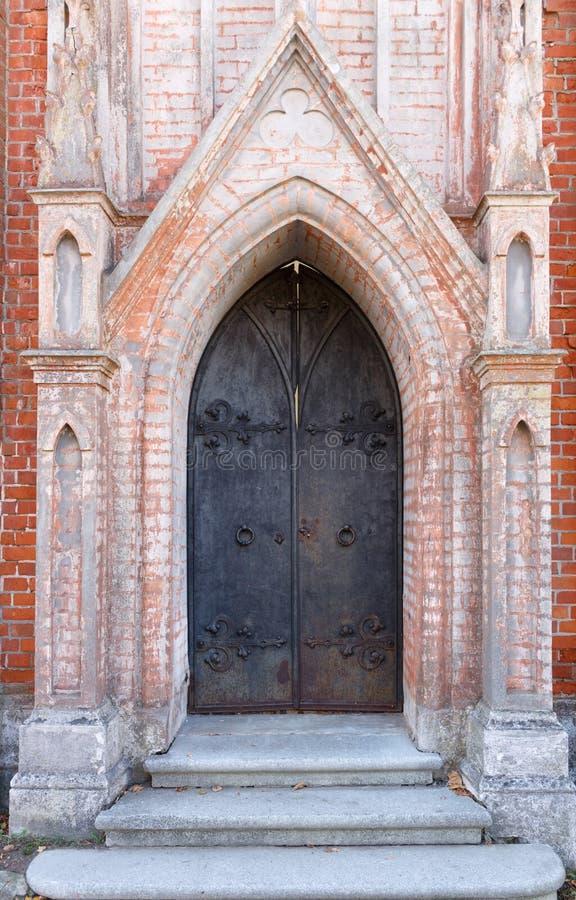 Oude metaalpoorten of deur van oude rode baksteenkerk royalty-vrije stock afbeelding