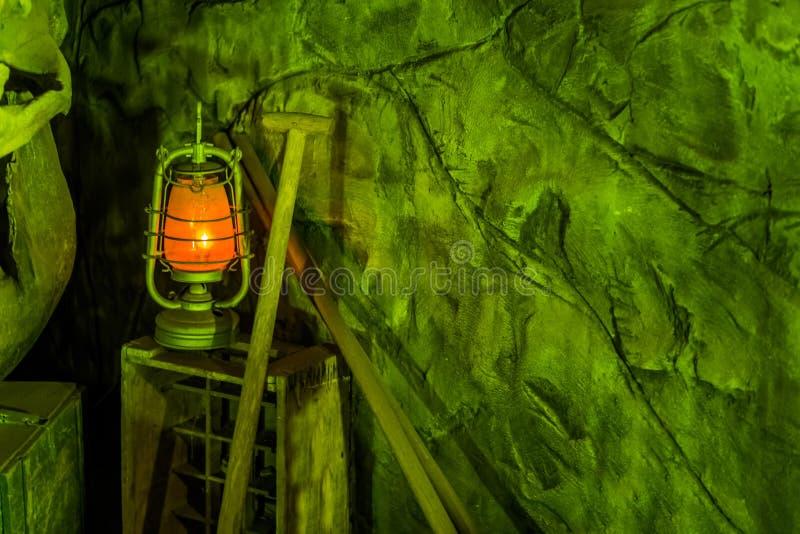 Oude mijnwerkersachtergrond met een aangestoken lantaarn en schop, een ondergronds in een goudmijn stock foto