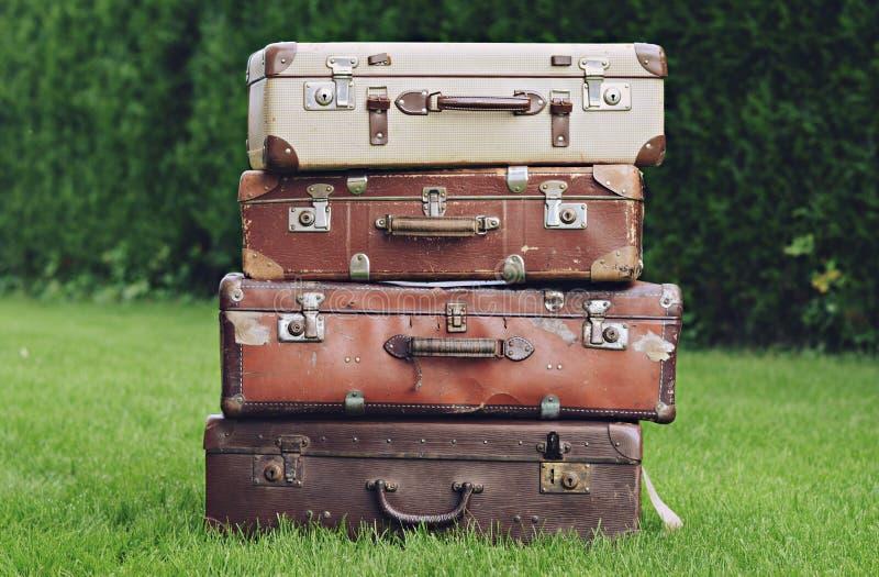Oude modieuze bruine koffers op de tuin stock afbeeldingen