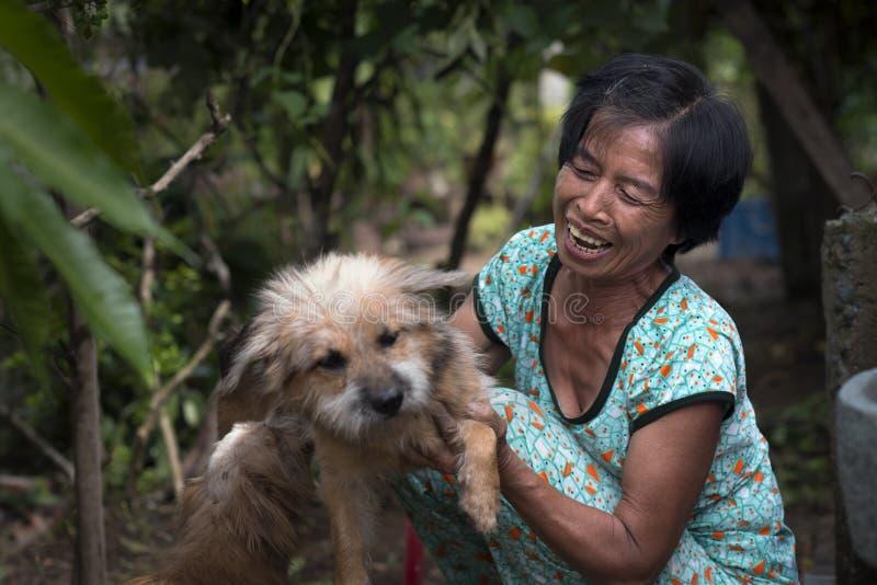 Oude mooie Vietnamese vrouw met haar hond in Mekong gebied, Vietnam stock afbeeldingen