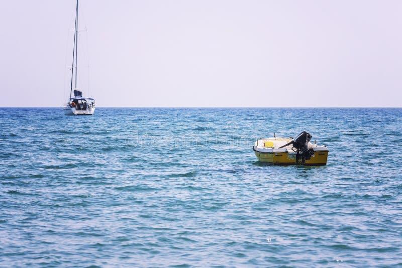 Oude motor en zeilboten in het overzees tegen de achtergrond van bergen, wellustige zonnige middag stock fotografie