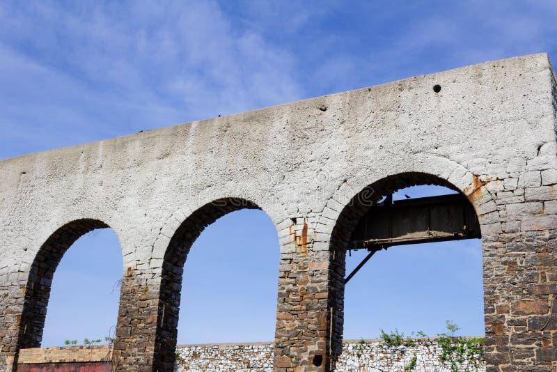 Oude muur met drie open overwelfde galerijen dat zodra vensters, verlaten de bouwruïnes hield stock foto