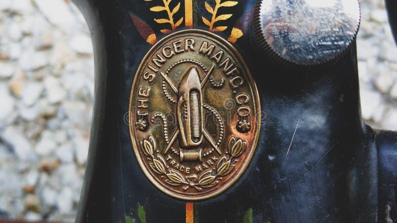 Oude naaimachine uitstekende retro dichte omhooggaand Zanger Factory Emblem stock afbeeldingen