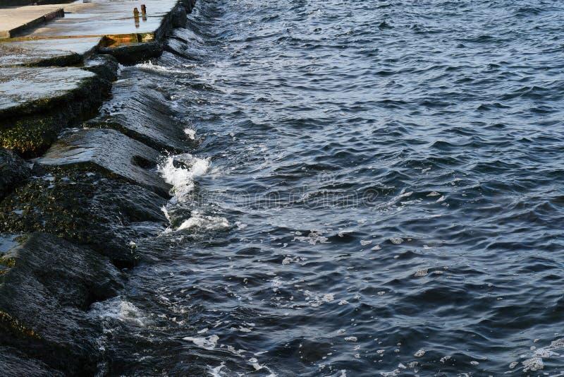 Oude natte dijk en donkerblauw water stock foto's