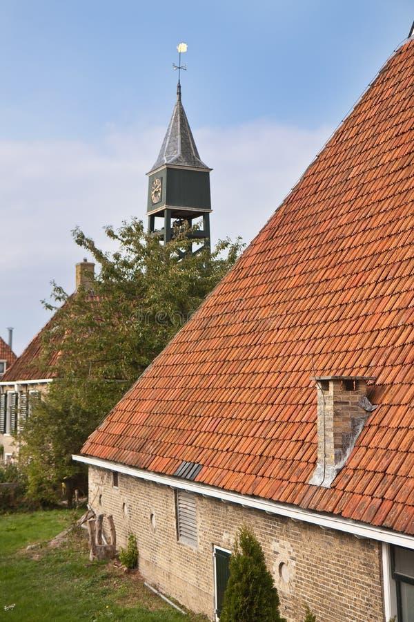 Oude Nederlandse boerderij met churchtower achter het stock foto