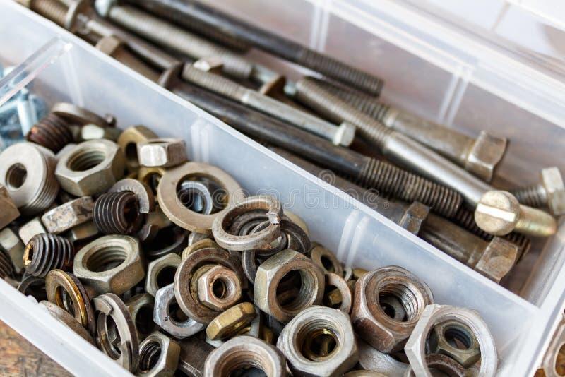 Oude noten - en - bouten in een opslagdoos stock foto