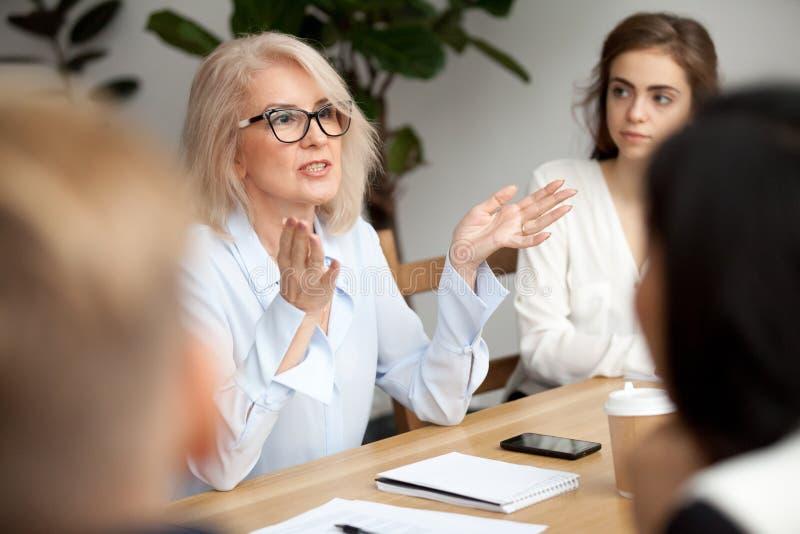 Oude onderneemster, leraars of bedrijfsbus die aan jongelui spreken stock afbeelding