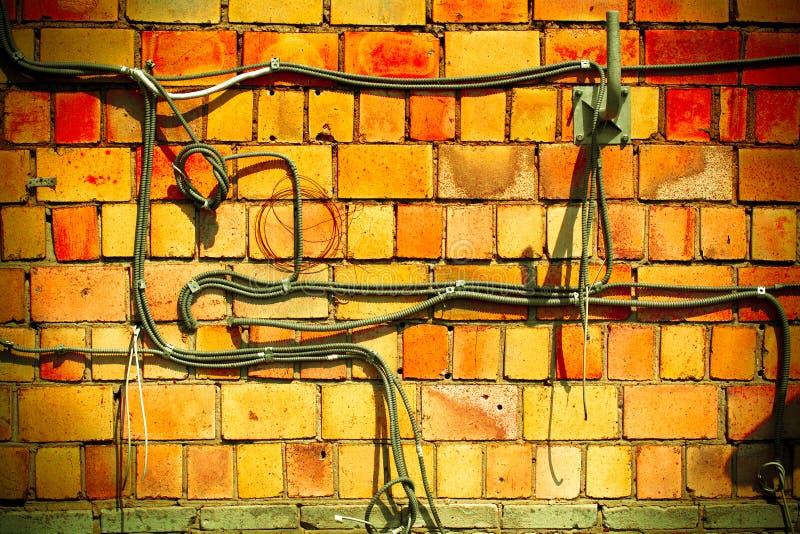 Oude oranje bakstenen muur. Communicatie kabels stock afbeeldingen