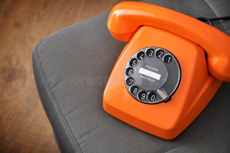 Oude oranje telefoon met wijzerplaat royalty-vrije stock afbeelding