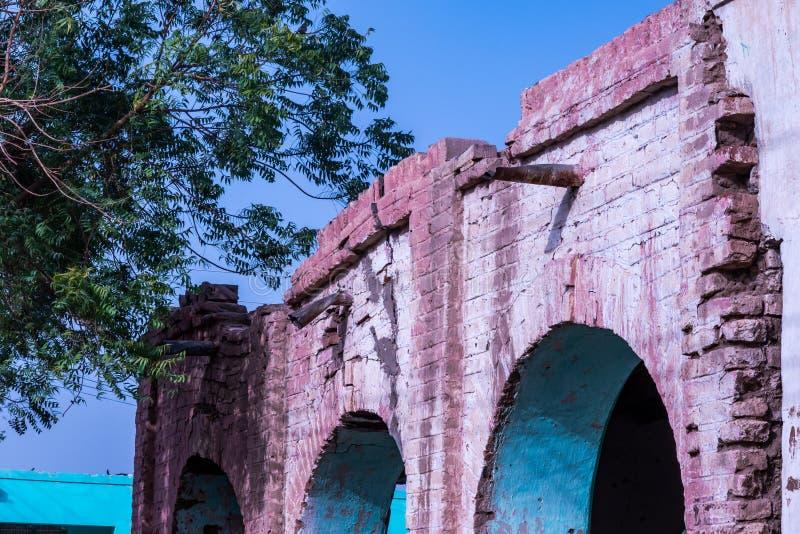 Oude overspannen pijler in een Afrikaans dorp met open downpipe en afschilferende roze en een turkooise verf stock foto