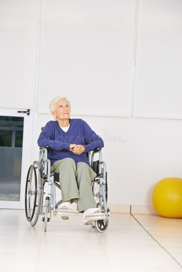 Oude peinzende vrouwenzitting in rolstoel stock afbeeldingen
