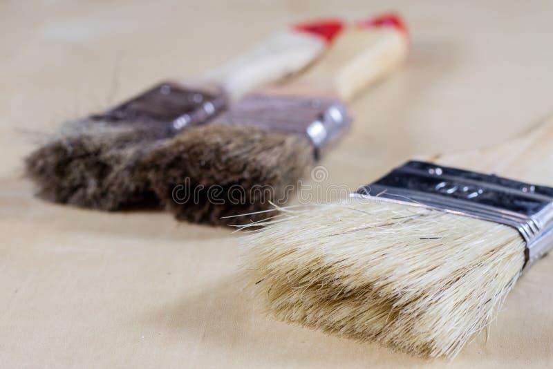 Oude penselen voor verf, Blikken van verf op houten lijst verf stock afbeelding