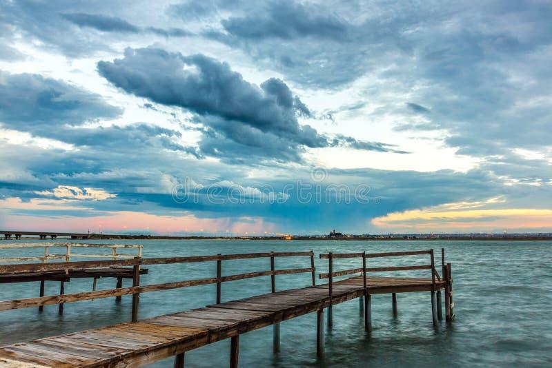 Oude Pier op een Rivier met Stadslichten op de Achtergrond royalty-vrije stock foto's