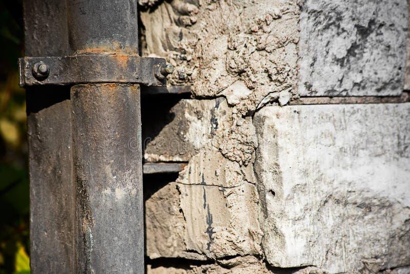 Oude pijp in bijlage aan de vernietigde muur stock afbeelding
