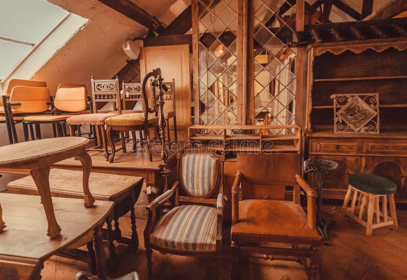 Oude planken en houten meubilair in historisch huis met uitstekende stoelen en decoratie royalty-vrije stock afbeeldingen