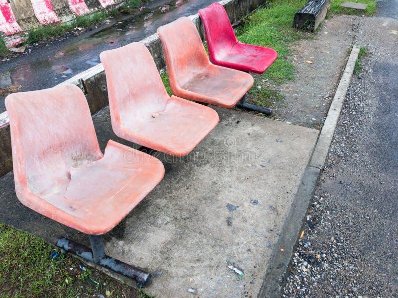 Oude plastic stoel op de metaalrij stock afbeeldingen