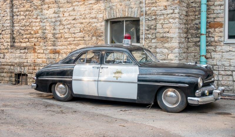 Oude politiewagen en leisteenmuur stock foto