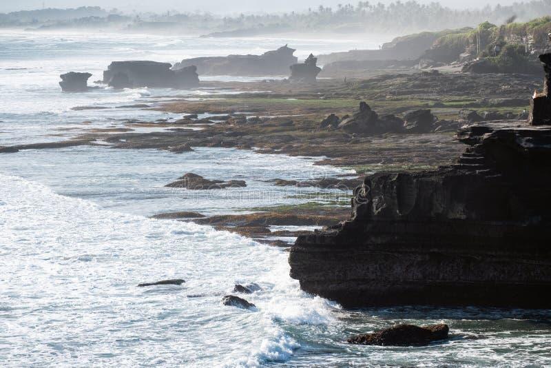 Oude Pura Batu Bolong-tempel op rotsachtige berg bij kustlijn stock foto's
