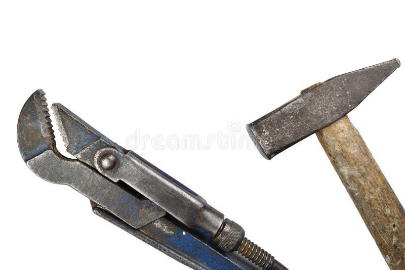 Oude regelbare moersleutel en hamer stock afbeelding