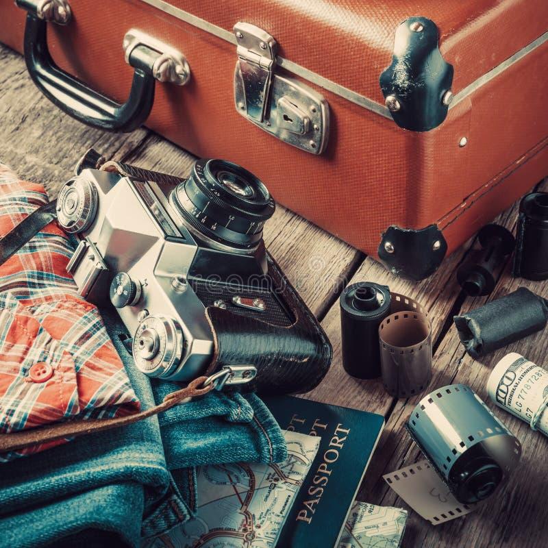Oude reiskoffer, tennisschoenen, kleding en retro camera stock afbeeldingen