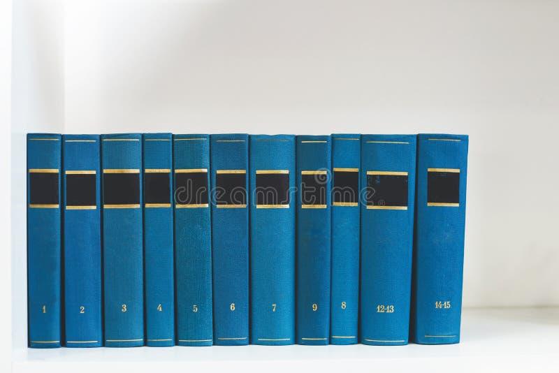 Oude retro boeken met kleurendekking op een wit planken vooraanzicht Selectieve nadruk stock afbeelding