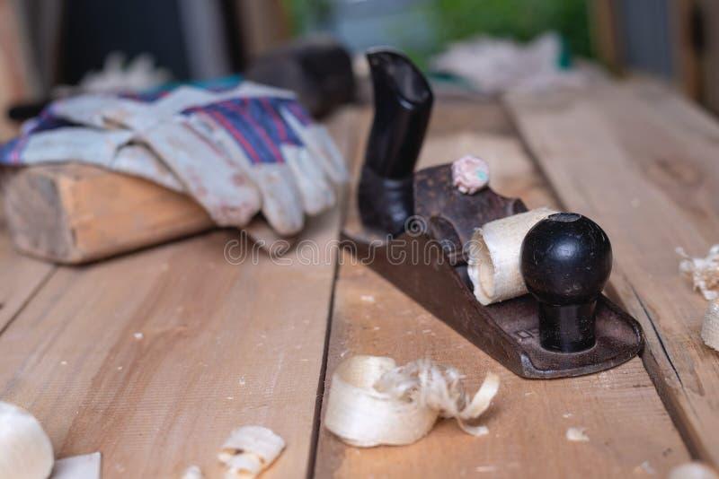 Oude retro handplaner met handschoenen en houten hamer op houten lijst met zaagsel en spaanders timmerwerk, houten dakwerk, houte stock fotografie