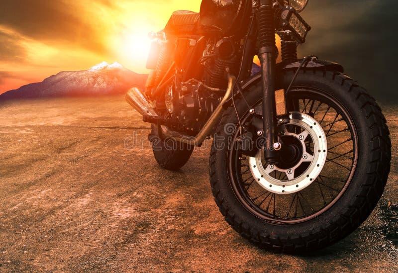 Oude retro motorfiets en de mooie achtergrond van de zonsonderganghemel stock foto's