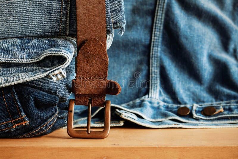 Oude riem en jeans op houten stock afbeeldingen