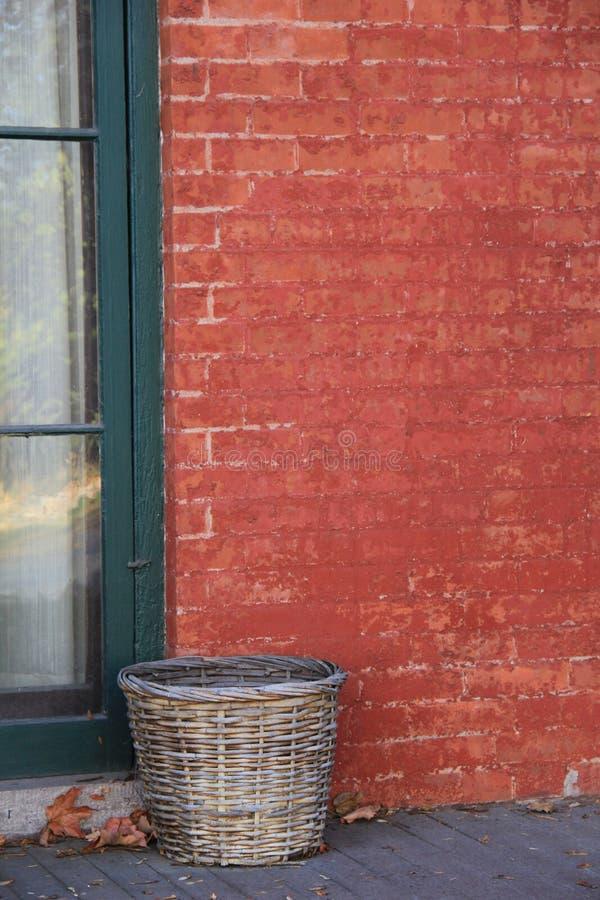 Oude rode baksteen en geweven mand stock fotografie
