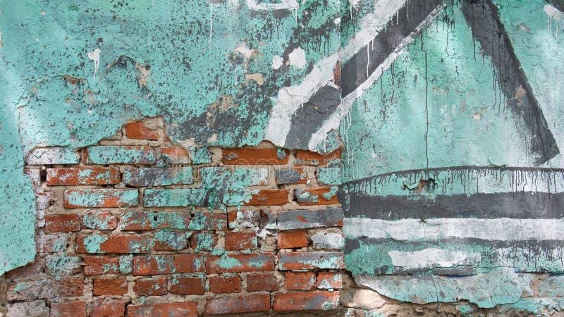 Oude rode bakstenen muur met barsten en oude turkooise verf stock afbeelding
