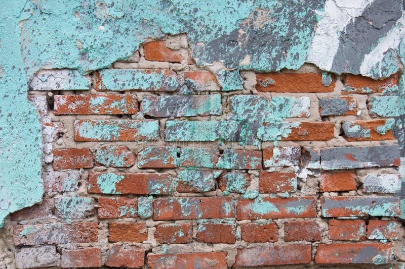 Oude rode bakstenen muur met barsten en oude turkooise verf stock foto