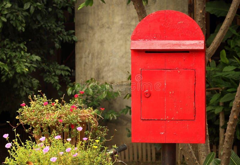 Oude rode brievenbus in de tuin stock afbeelding