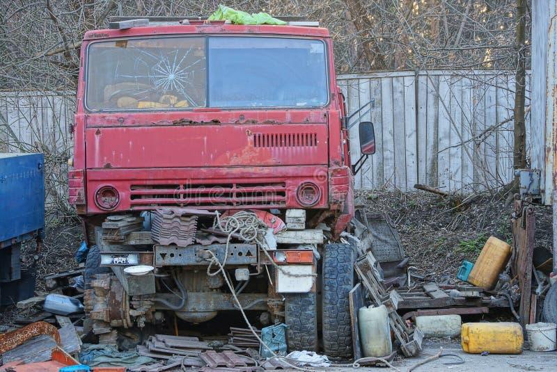 Oude rode cabine van een gebroken vrachtwagen en vervangstukken op de straat in een stortplaats royalty-vrije stock afbeelding