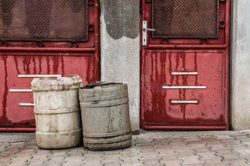 Oude rode deuren met huisvuilmanden royalty-vrije stock fotografie