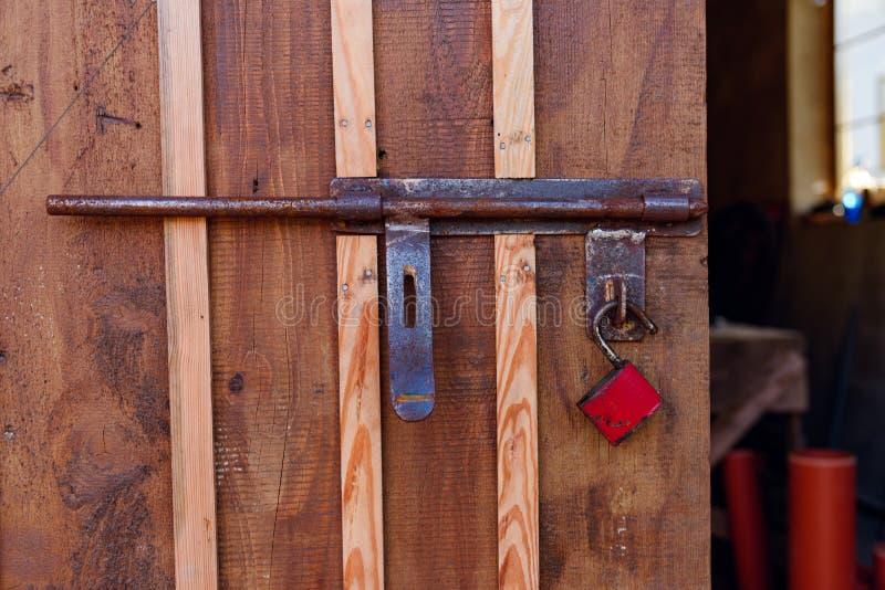 Oude rode hangslot op een houten deur stock foto