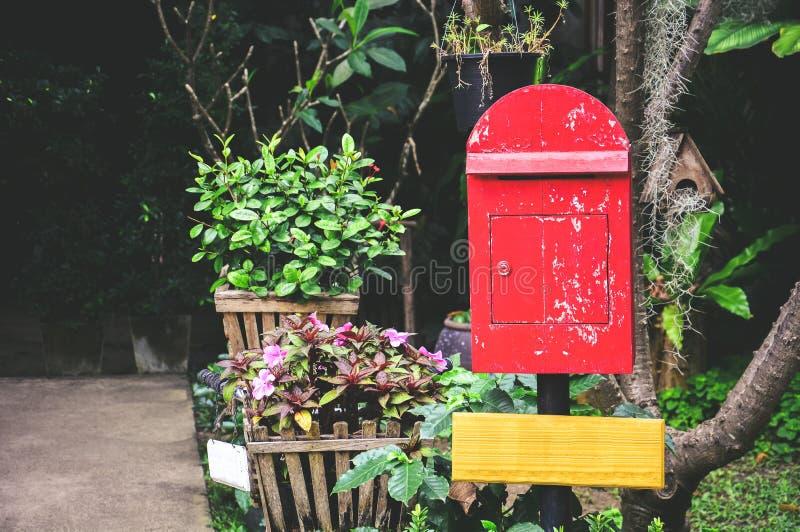 Oude rode houten brievenbus op zwarte pilaar met blanco geel houten bord op de achtergrond van de tuin, exemplaarruimte stock foto's