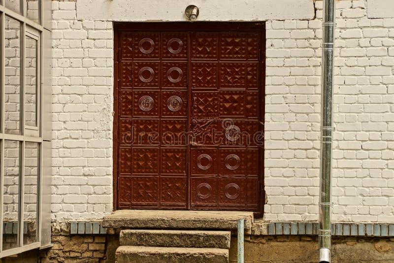 Oude rode metaaldeuren op een grijze bakstenen muur royalty-vrije stock fotografie