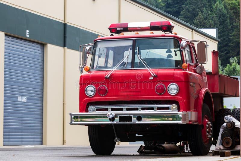 Oude rode ontmantelde die brandmotor in een industrieel complex wordt geparkeerd stock foto