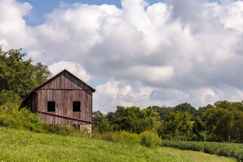 Oude rode schuur op een heuvel stock fotografie