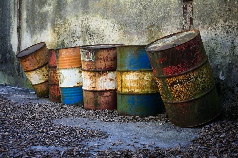 Oude roestige afvalvaten door het overzees stock foto