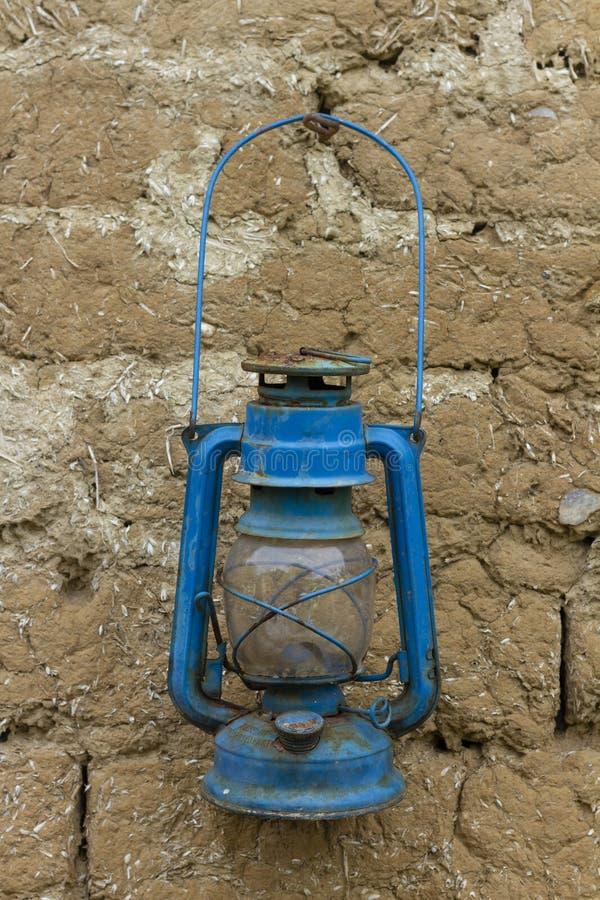 Oude roestige blauwe aardolielantaarn op een modderbakstenen muur royalty-vrije stock fotografie