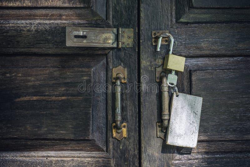 Oude roestige en zeer belangrijke sloten op houten deur stock foto's