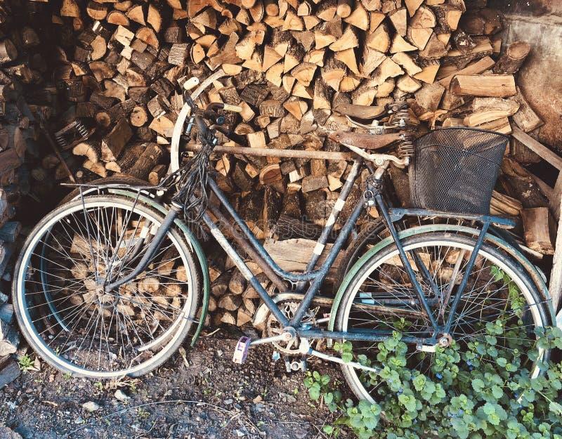 Oude roestige fietsen die ongebruikt lange tijd op brandhout achtergrondwijnoogst zijn stock afbeelding