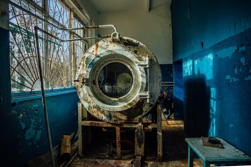 Oude roestige gebroken industriële wasmachine met schilverf in wasserijruimte bij het verlaten psychiatrische ziekenhuis royalty-vrije stock foto's