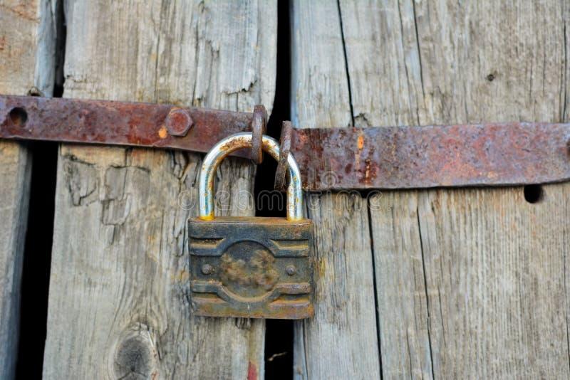 Oude roestige hangslot en ketting op de landelijke houten poort stock afbeeldingen
