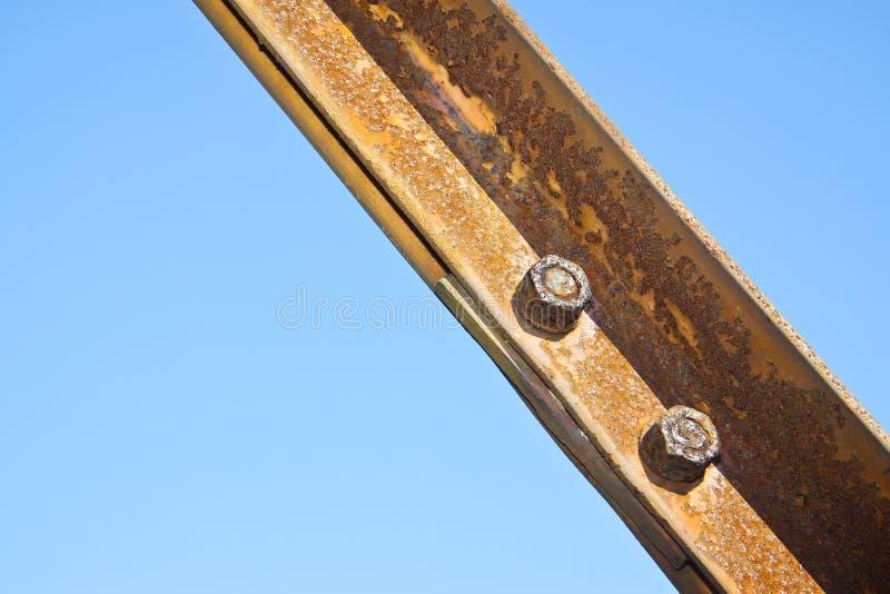 Oude roestige ijzerstructuur met vastgeboute metaalprofielen tegen een blauwe hemel stock foto's